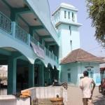 3.Seseorang melintas di tengah-tengah antara masjid dan pohon bidara yang dikelilingi makam kuno.